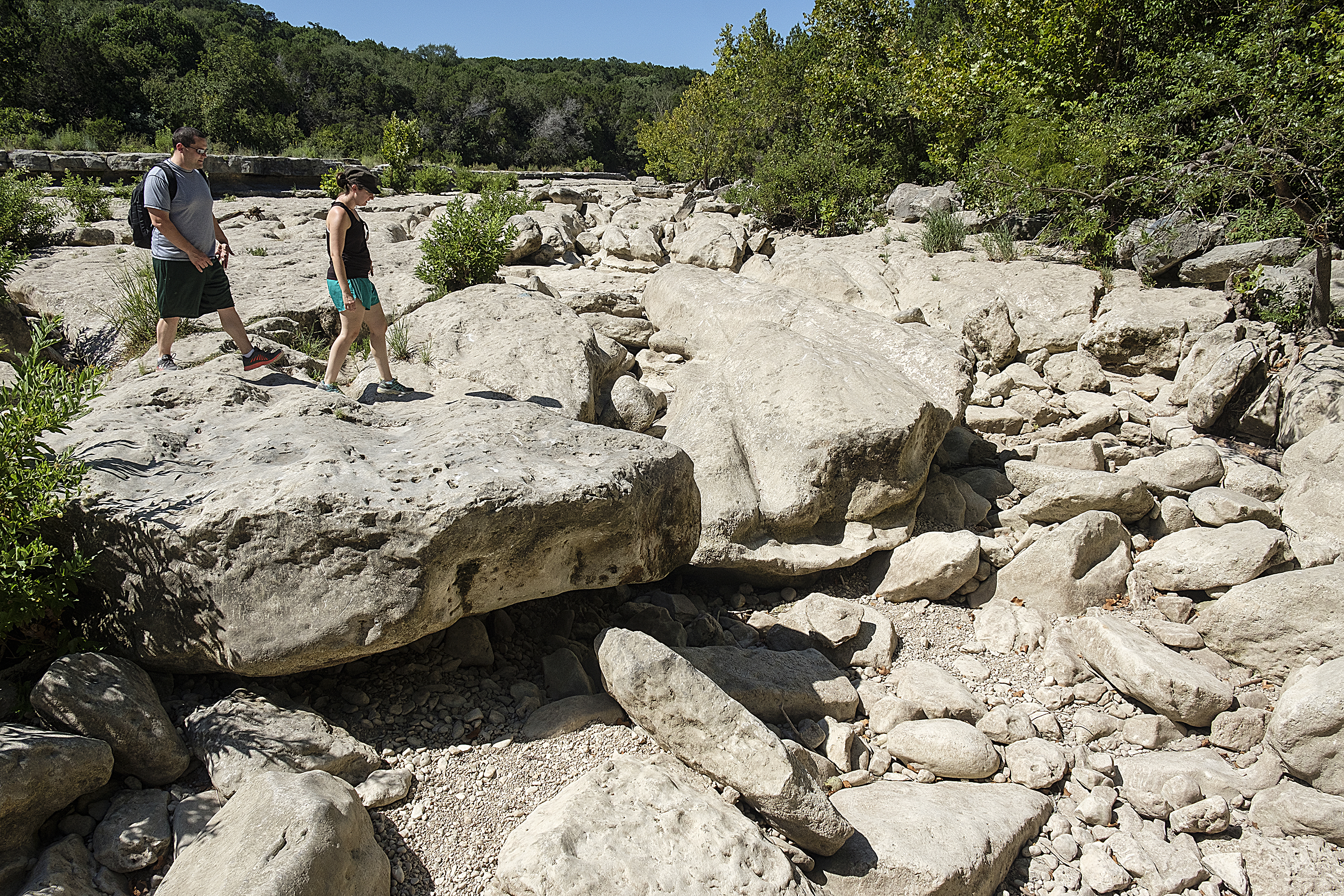 07-27-2017 -- A couple walks among the boulders near Campbell's Hole on the Barton Creek Greenbelt. Photo © Alberto Martinez