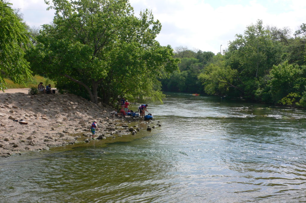 People sitting on the banks of Barton Creek